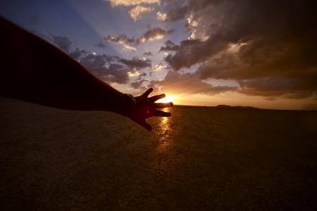 太陽 - 太陽をカバーしようとすると、男性の手。 写真素材