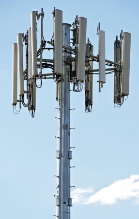 decibels: Modern Cellular Tower - Communication Tower on Blue Sky. Vertical Photography.