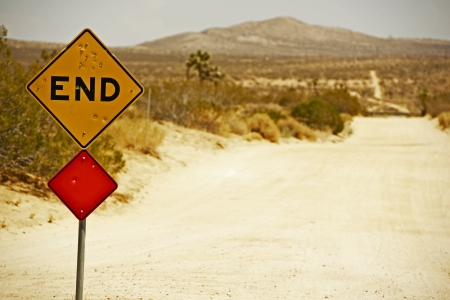 end of road: End Traffic Sign with Bullet Holes. Somewhere in Southern California Mojave Desert. Dirty Dusty Country Road Stock Photo