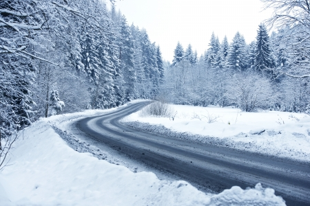 icy conditions: Winter Forest Road - Mountain Road Covered by Snow. Winter Theme. Winter Photography Collection. Stock Photo