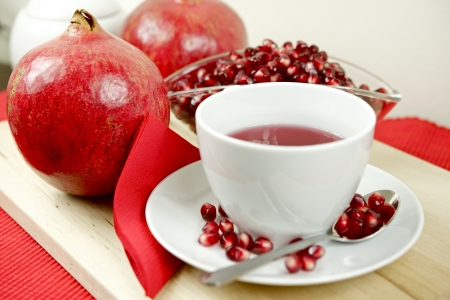 Pomegranate Tea, Fruits and Pomegranate Seeds on Wood Board. Healthy Pomegranate Tea in the White Cup. Food and Drinks Photo Collection. Stok Fotoğraf