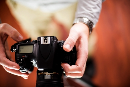 photo studio: Professional Camera in Hands of Photographer. Photography Theme. Top View - Male Hands. Technology Photo Collection. Stock Photo
