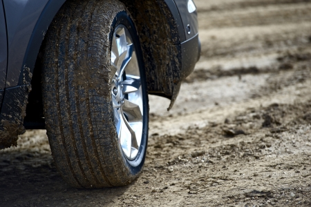 On the Dirty Road. Brand New SUV Wheel on the Muddy Road. Wheel Closeup. Off-Road Theme. Transportation Photo Collection.