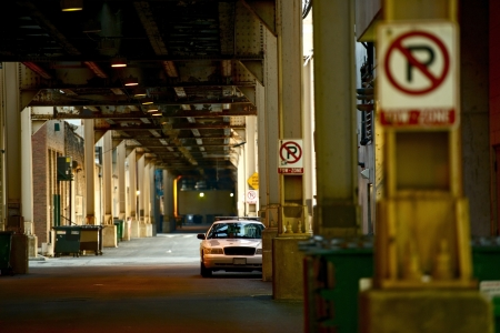 city alley: Downtown Chicago Alley Under Train Tracks and Police Cruiser Parked in a Distance. No Parking Signs. Chicago Urban Photography Collection.