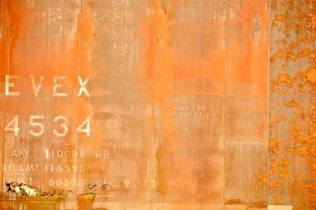 オレンジ色のさびた背景。いくつかの文章でさびた金属の質感。背景写真集。