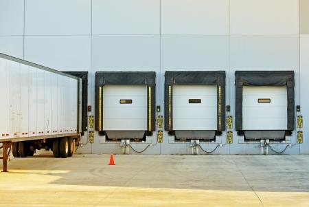 半トラック トレーラー倉庫ロードアンロードします。大きい現代アメリカの倉庫の建物。出荷および貨物写真集。