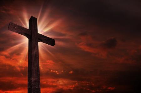 日没の十字架。明るい光の十字架上クロス。暗い赤の曇り空。キリスト教のテーマです。