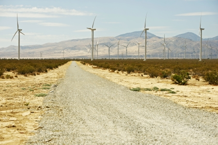 Rough Desert Road. gravel Road in Mojave Desert California. Wind Turbines Ahead.  photo