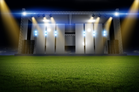 Music Stage on the Field - Stage on the Meadow. Concert Scene Illuminated by Colorful Light Beams. Stock Photo