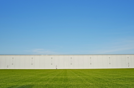 Large Warehouse Building and the Grass Field. Industrial Zone. photo