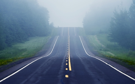 driving conditions: Foggy Road Ahead. Road Through Minnesota Wilderness.  Stock Photo