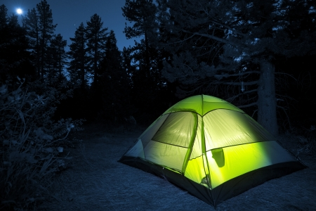 Small Camping Tent Illuminated Inside. Night Hours Campsite. Recreation and Outdoor Photo Collection. Stock Photo