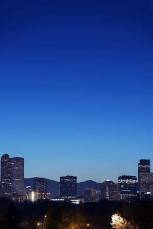 denver skyline with mountains: View Of The Denver Skyline At Twilight - Vertical Photography. Denver, Colorado, United States.