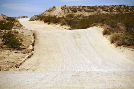 Sandy Desert Road in Mojave Desert, California, United States. Back Country Bumpy Road. Stock Photo