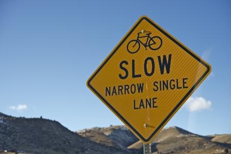 slow lane: Slow Sign for Bikers. Slow - Narrow Single Lane Yellow Traffic Sign Closeup.