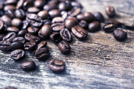 Scattered Coffee Beans on Vintage Wood Table Closeup.