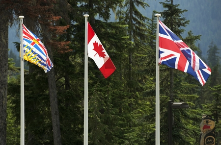 Three Canadian Flags. British Columbia, Canada National and British National Flag. Tree Large Flags on Poles. photo