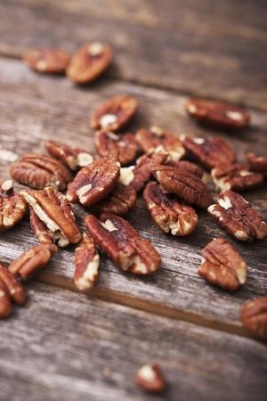 pecans: Fresh Tasteful Pecan Nuts on Wooden Table. Stock Photo
