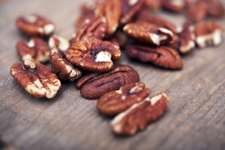 Fresh Pecans on VIntage Wood Table Closeup. Stock Photo