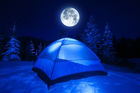 Winter Night Camping in Heavy Mountains Snow. Large Full Moon on the NIght Sky. Outdoor and Recreation Theme. photo