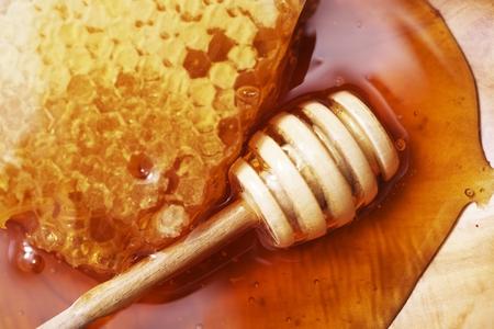 abejas panal: Panal con cucharón de madera en el primer de la placa de madera Foto de archivo