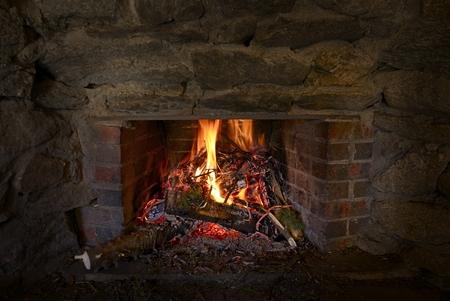 stone fireplace: Burning Wood in Stone Fireplace. Fireplace Closeup.