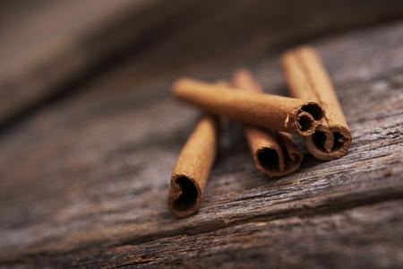 Reclaimed: Raw Organic Cinnamon Sticks on Aged Wood Table.