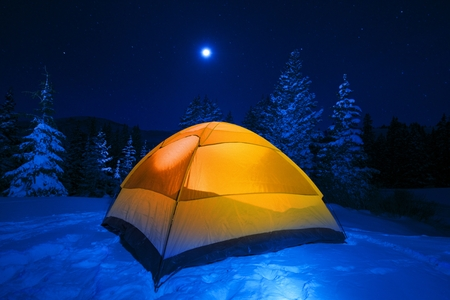 Winter Tent Camping in Colorado Wilderness. Cold Snowy High Country Night in Small Orange Tent.  photo