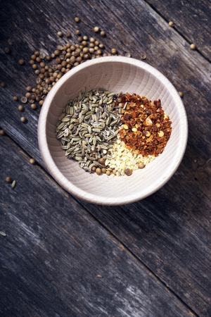 Spices in Small Wooden Bowl on Aged Wood Table, Stock Photo