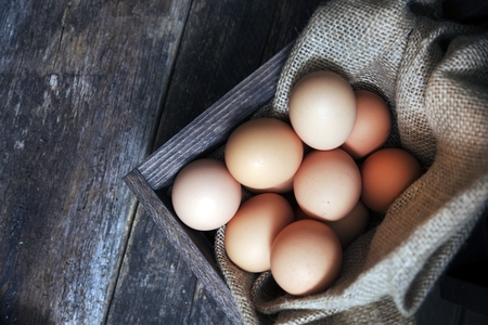 cholesterol free: Fresh Eggs in Small Wooden Crate with Canvas on Aged Wooden Table. Fresh Organic Cage Free Chicken Eggs.