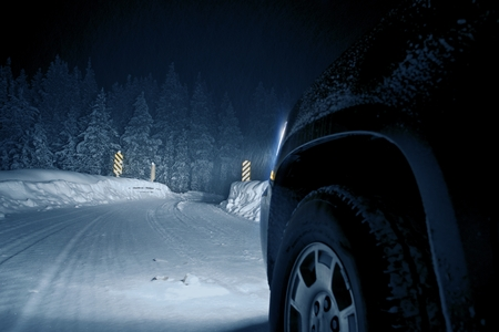night road: Dangerous Winter Road at Night. Colorado Road Drive in Snow Storm. Stock Photo