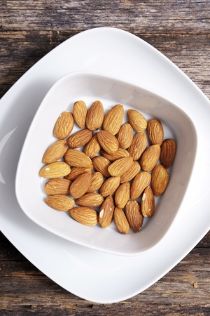 Tasty Almond in White Bowl on Wooden Table. View From Above. 免版税图像
