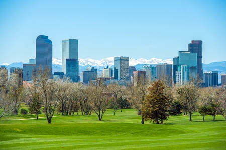 Sunny Denver Skyline. Spring in Colorado. Denver Skyline and Snowy Rocky Mountains.  Stock Photo