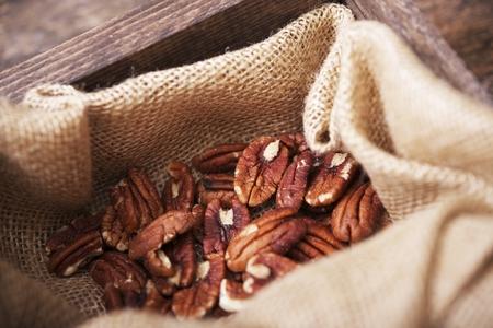 pecans: Pecans in Linen and Wooden Crate Closeup. Fresh Pecans.