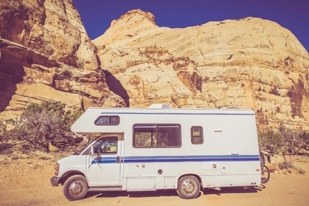 rv: Vintage Camper in Utah Sandstone Canyon. Class C Recreation Vehicle. Vintage Color Grading. Stock Photo