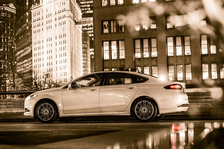 White Luxury Car on Streets of Chicago. Browny Golden Color Grading. Transportation Concept. Chicago, United States. Stock Photo