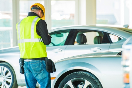 Car Dealer Client. Construction Worker Looking For a New Car in Dealership Showroom. photo