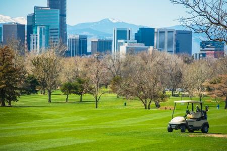 Colorado Golf Field with Denver Skyline and Golf Cart. Stock Photo