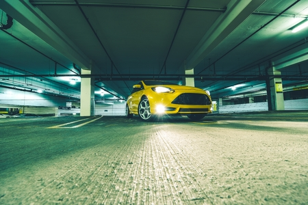 The Parking Space. Yellow Sports Car in Underground Parking at Night. Editorial