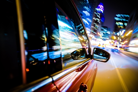 drive through: Driving Through City Lights. Car Side and Mirror View. Night Drive Concept Stock Photo