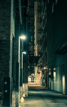 dark: Dark and Spooky Chicago Alley in Greenish Color Grading. Vertical Chicago Alley Photo.