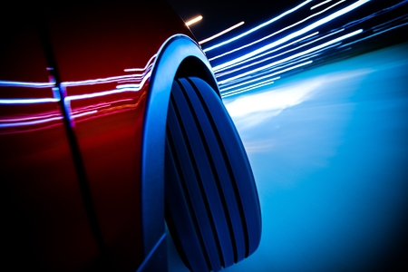 curve: Night Ride Blurs. Car Front Wheel on the Road Curve Closeup with Long Exposure Blurs. Stock Photo