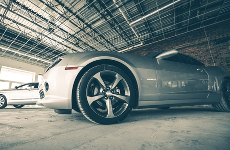 car in garage: Silver American Muscle Car Under the Unfinished Metal Roof   Stock Photo