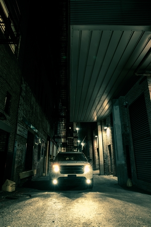 headlights: Dark Alley Drive. American City at Night. SUV on the Alley Stock Photo