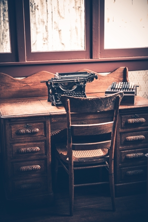 vintage furniture: Ghostwriter Desk. Vintage Desk with Aged Typewriter and Wooden Ghostwriter Chair. Stock Photo