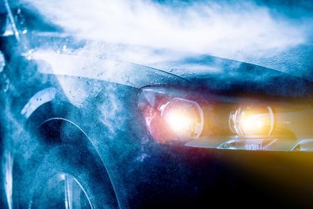 높은 비 자동차 운전 차량 헤드 라이트의 근접 촬영. 비가 폭풍. 교통의 개념입니다.