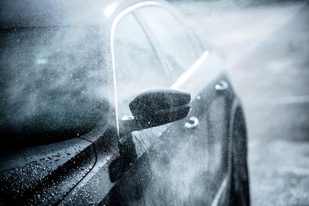 autolavaggio: Gentle lavaggio auto. Moderna Compact Car coperto da acqua. Blu scuro color grading.