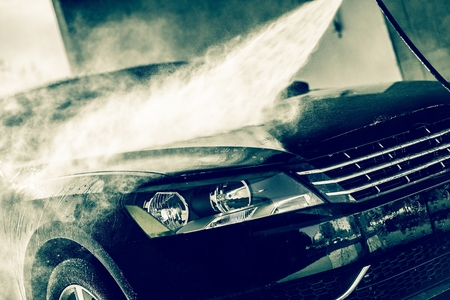 soaping: Car Wash Closeup. Washing Modern Car by High Pressure Water.
