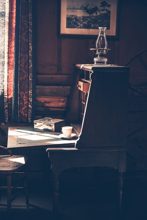xx century: Vintage Wooden Desk in the Dark Room. Early XX Century Room Interior