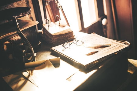 old desk: Vintage Desk with Glasses. Aged Wooden Desk, Old Books and Documents, and Vintage Desk Accessories.